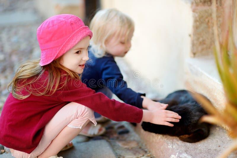 Download 2 маленьких сестры и кот Outdoors Стоковое Фото - изображение насчитывающей персона, кот: 41660528