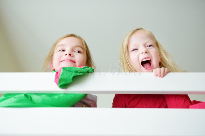 2 маленьких сестры околпачивая вокруг, играя и имея потеху в двойной двухъярусной кровати стоковые изображения rf