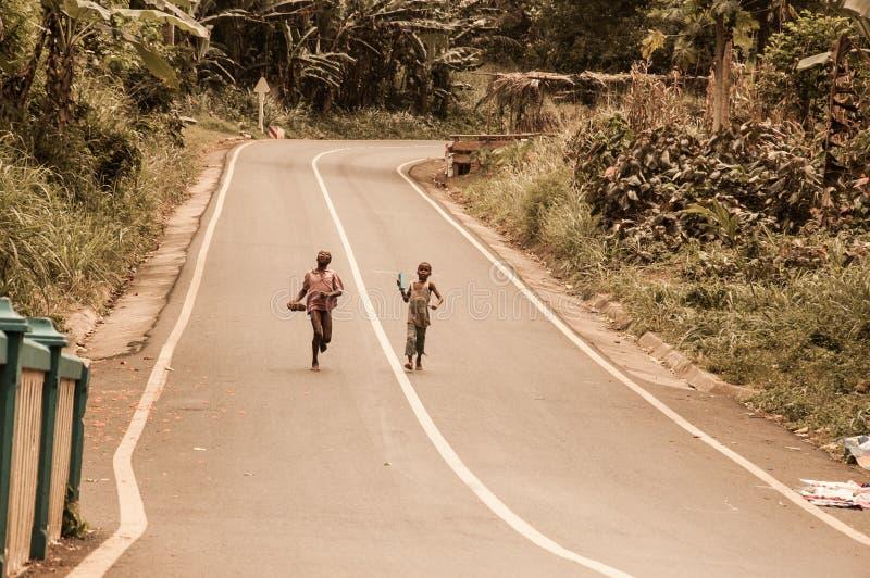 2 маленького ребенка бежать barefoot в улице стоковое фото rf