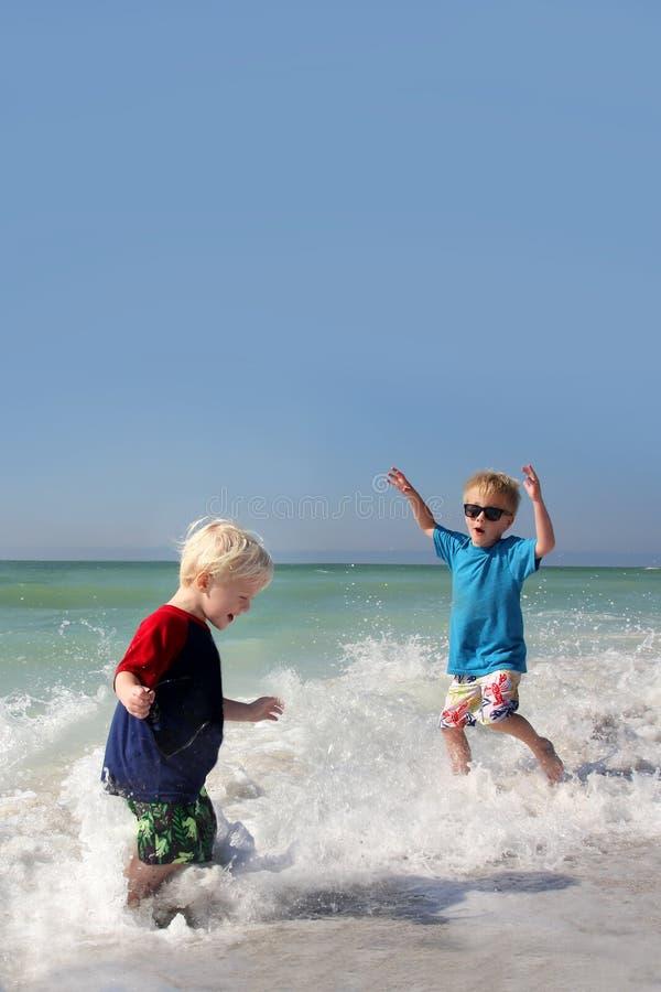 2 маленького ребенка играя и брызгая в воде океана стоковое фото