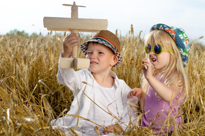 2 маленького ребенка играя с самолетом модели стоковое изображение rf