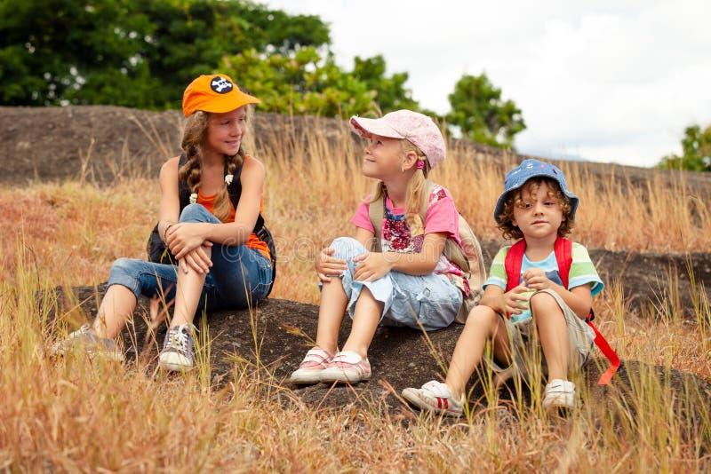 3 маленького ребенка при рюкзак сидя на тропе в m стоковые фото