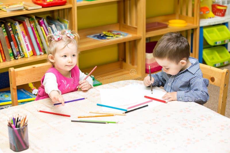 2 маленького ребенка рисуя с красочными карандашами в preschool на таблице Чертеж маленькой девочки и мальчика стоковое фото