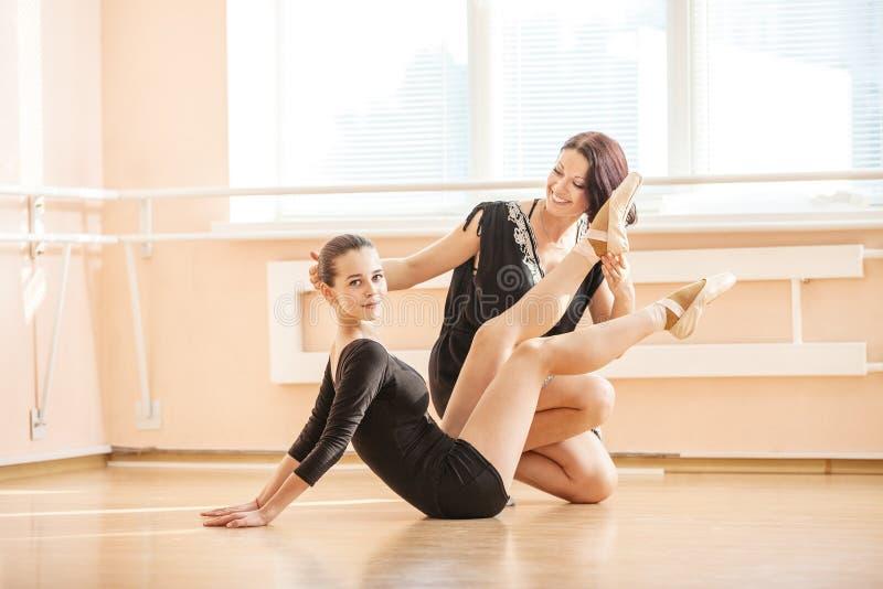 Маленькой девочке учителя балета показывающ как выполнить тренировку на поле стоковые фотографии rf