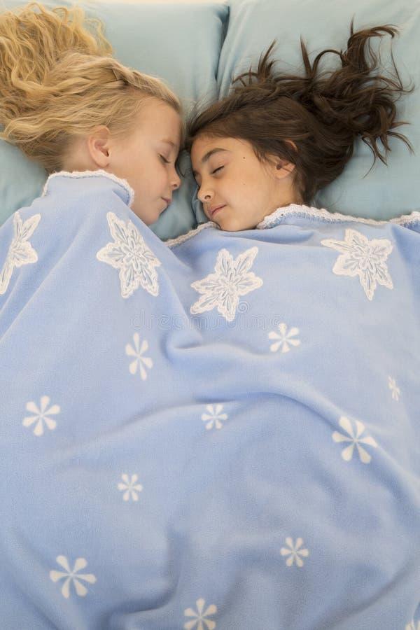 2 маленькой девочки в кровати уснувшей под одеялом снежинки стоковая фотография