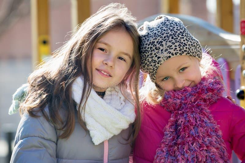 2 маленькой девочки представляя на спортивной площадке стоковая фотография