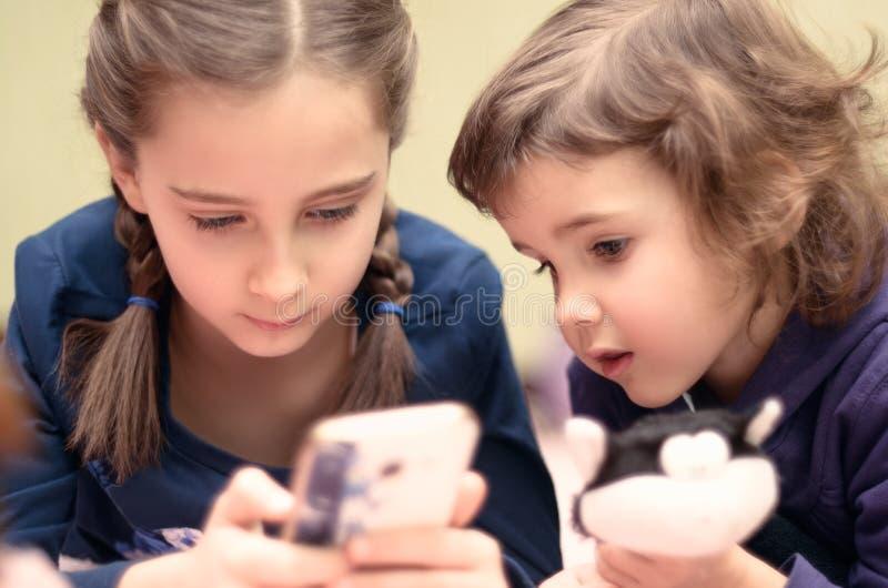 2 маленькой девочки при smartphone лежа на кровати дома стоковое изображение