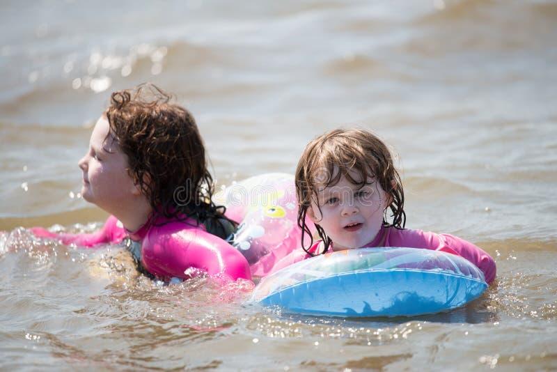 2 маленькой девочки плавая в автомобильные камеры в блаженном положении стоковые фото
