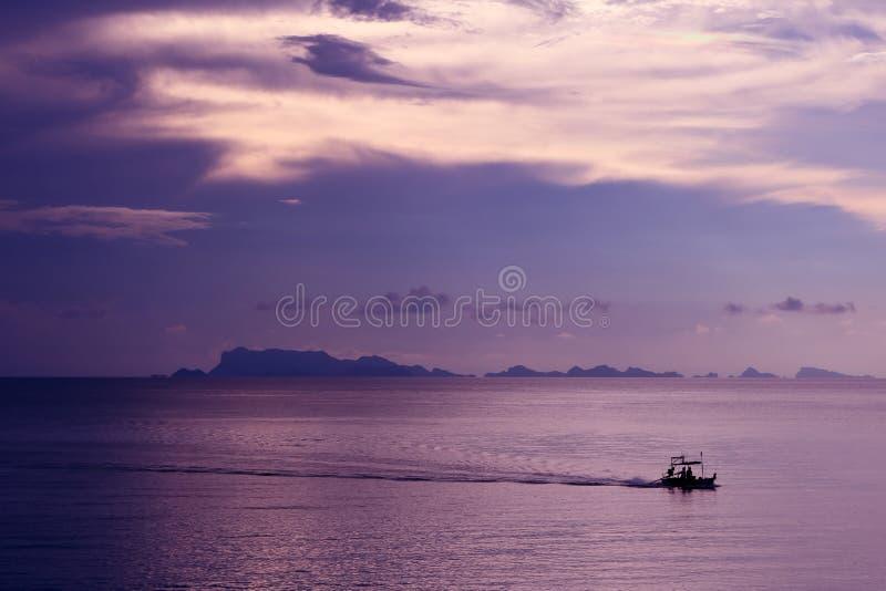 Малое плавание рыбацкой лодки в море с фиолетовым заходом солнца неба стоковое изображение rf