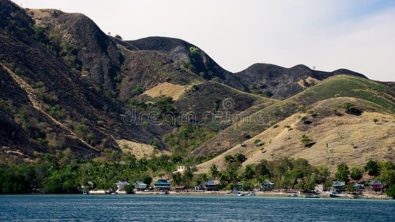 Малое строение домов в деревне на seashore на ноге горы заполнило с зеленой вегетацией стоковая фотография rf