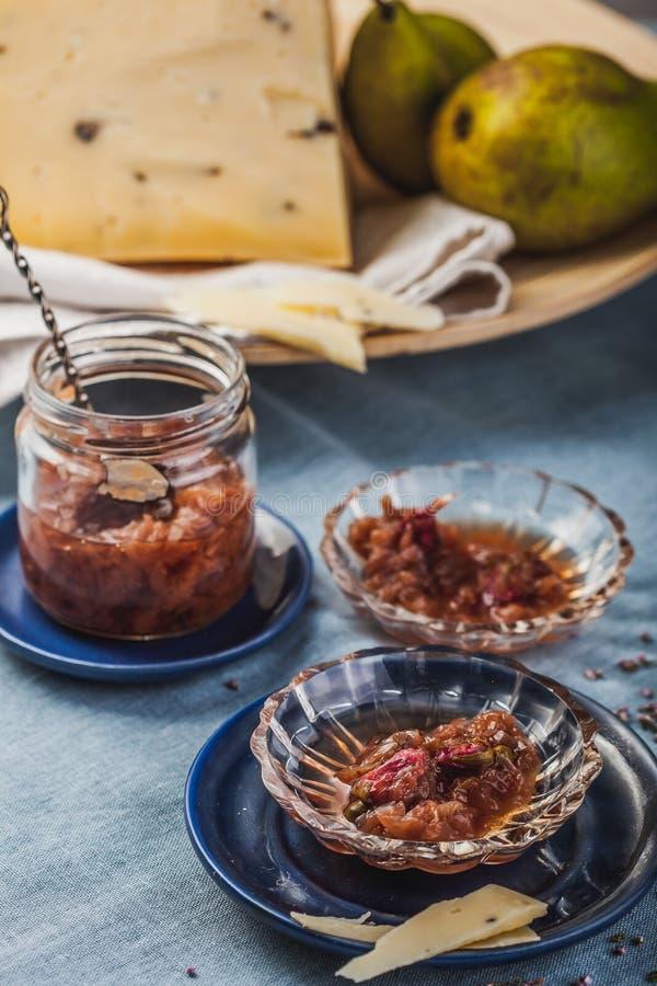 Малые блюда варенья с лепестком розы сжимают, груши и большая часть сыра на скатерти бирюзы стоковое изображение