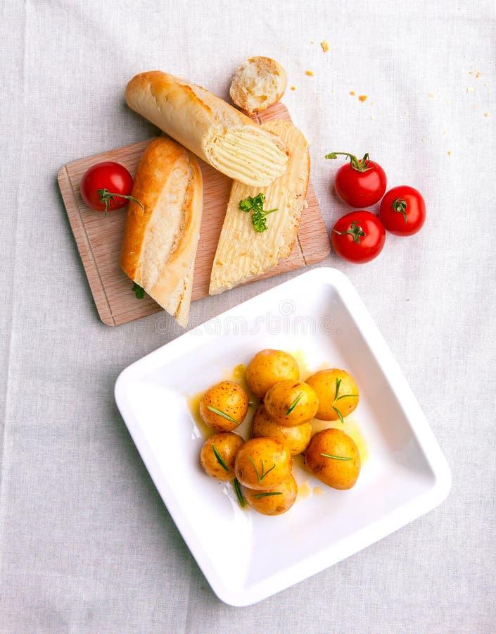 Малые новые кипеть картошки с багетом и овощами стоковое фото rf