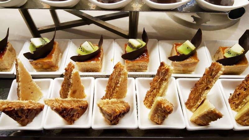 Малые сладостные десерты с шоколадом и кивиом в белых плитах стоковые фото