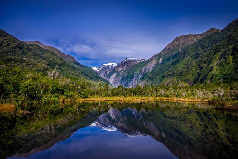 Малые peters пруда pond с отражением ледника Frantz Josef ледника горы в Новой Зеландии стоковые фотографии rf