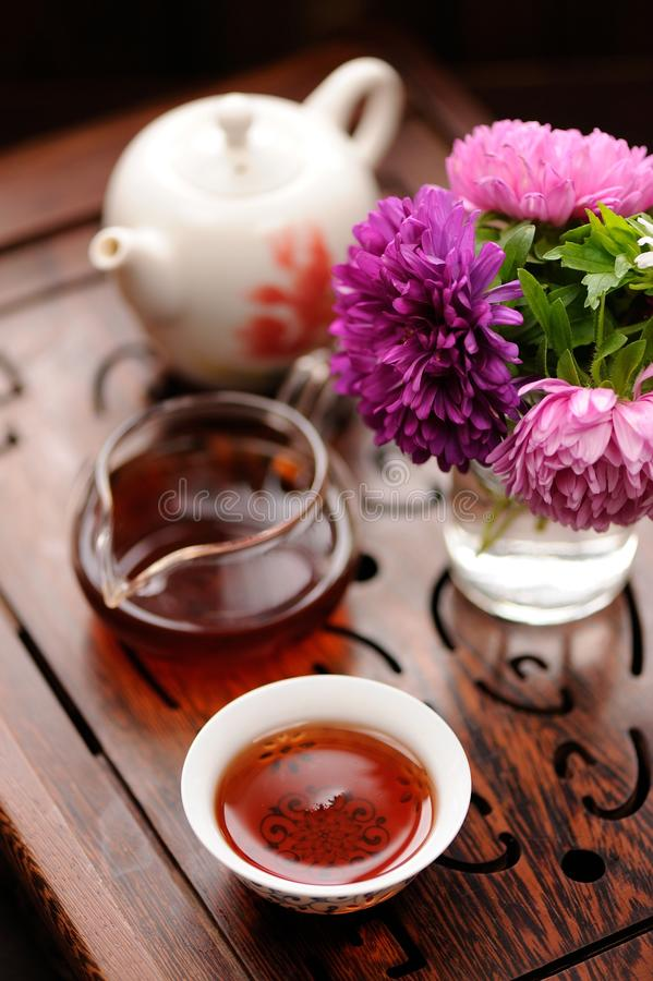 Малый букет фиолетовых и розовых астр и черного чая в китайце стоковая фотография