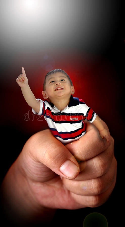 Малый мальчик в большой руке стоковое фото