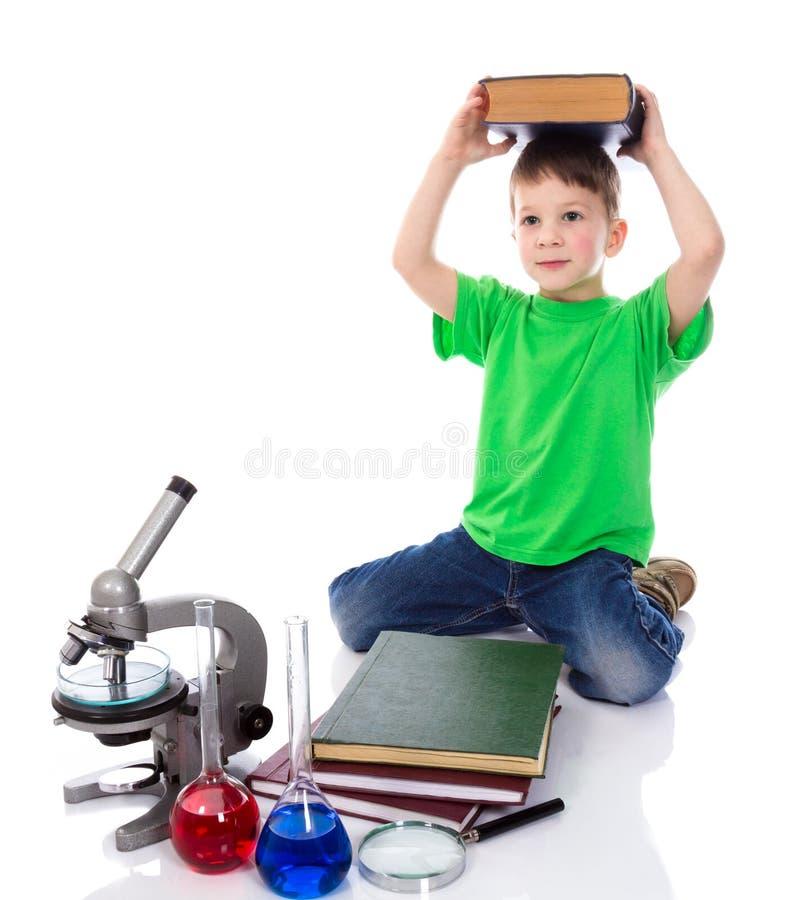 Малый мальчик держит большую книгу на его голове стоковая фотография rf