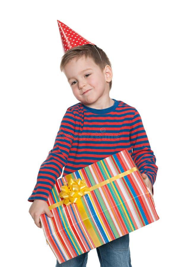 Малый мальчик держит подарочную коробку стоковое изображение