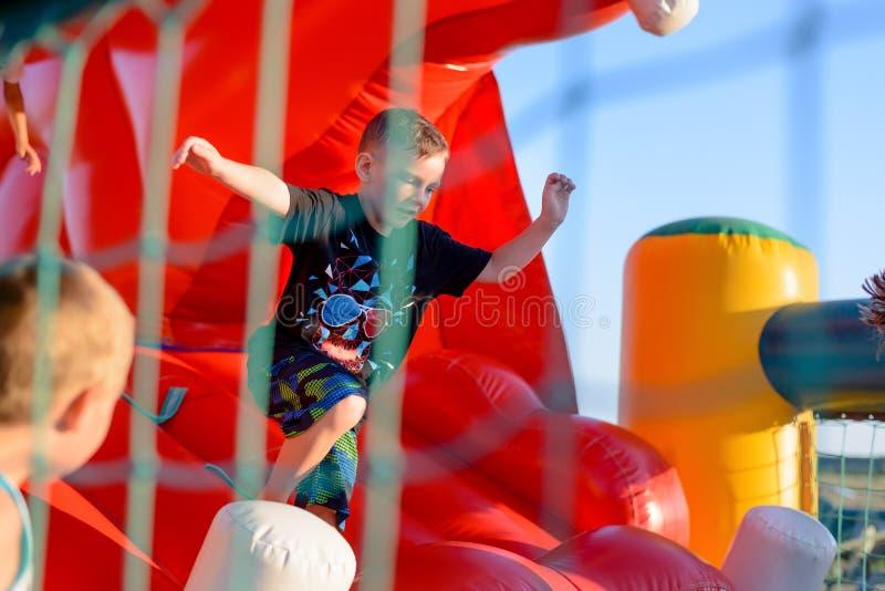 Малый мальчик играя на надувном замке стоковые изображения