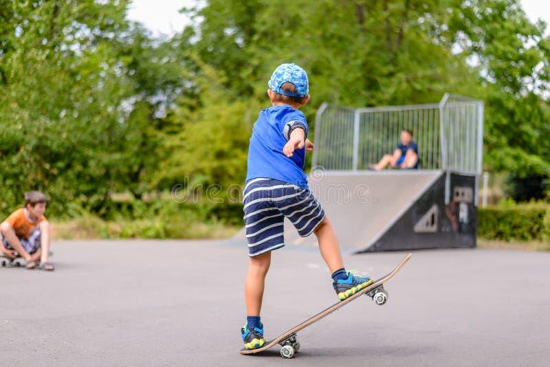 Малый мальчик играя с его скейтбордом стоковое фото
