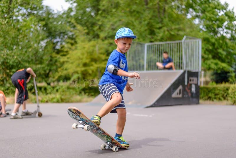 Малый мальчик играя с его скейтбордом стоковые фотографии rf
