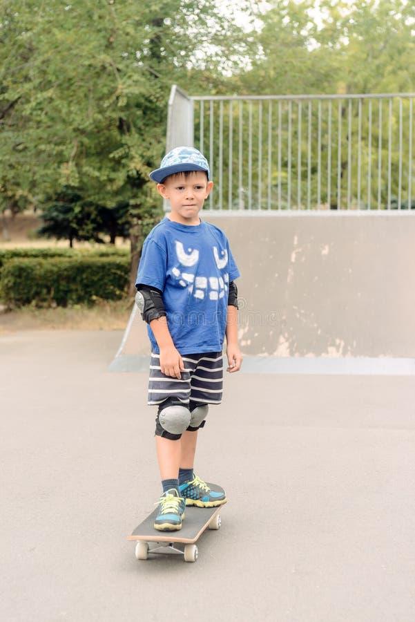Малый мальчик стоя на его скейтборде стоковое фото