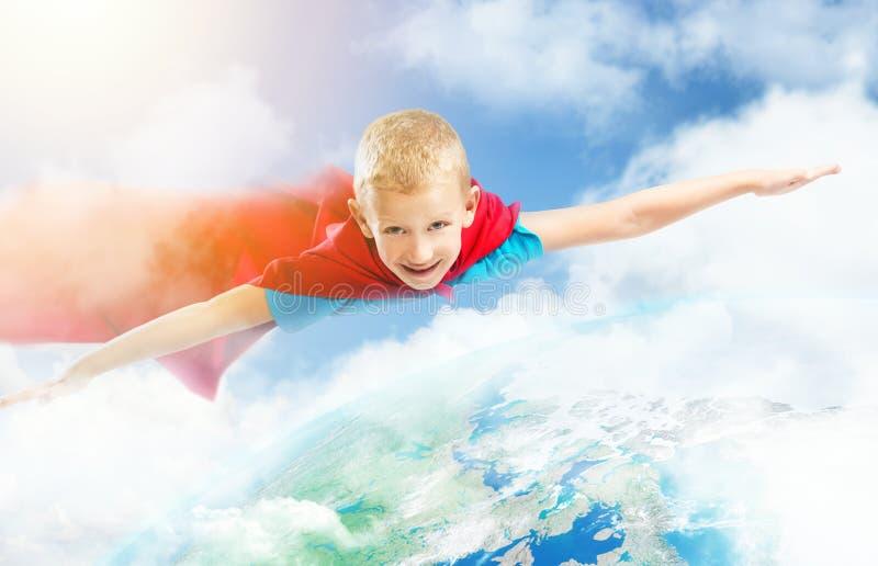 Малый мальчик супергероя летая над землей стоковое фото rf