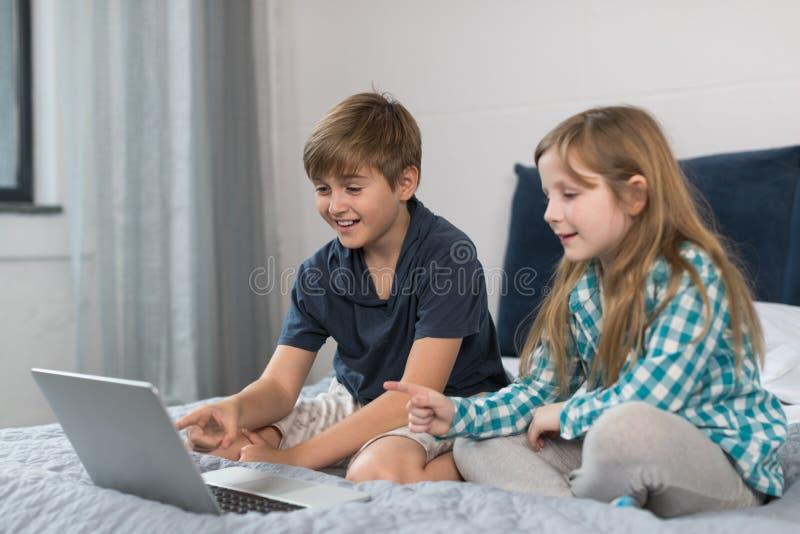 Малый портативный компьютер пользы мальчика и девушки сидя на кровати в интернете спальни, брата и сестры занимаясь серфингом стоковое фото rf