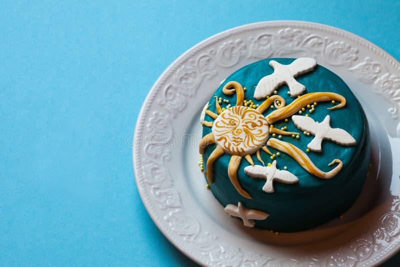 Малый торт пасхи голубой с желтым солнцем и белыми голубями в белой плите background card congratulation invitation стоковые изображения