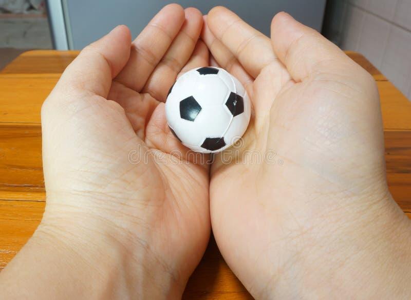 Download Малый футбольный мяч в обоих рука Стоковое Фото - изображение насчитывающей черный, кругло: 41659032