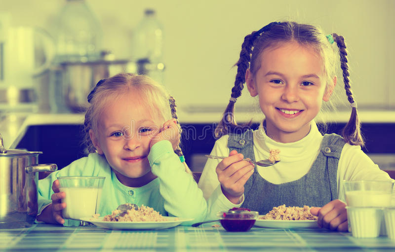 2 малых усмехаясь девушки есть здоровую овсяную кашу стоковые изображения rf