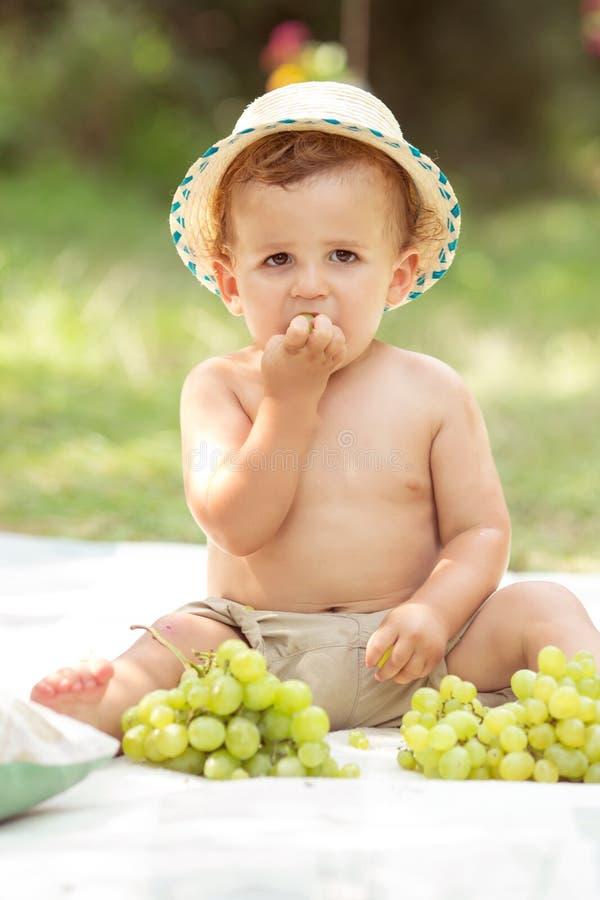 Малыш есть виноградины стоковая фотография