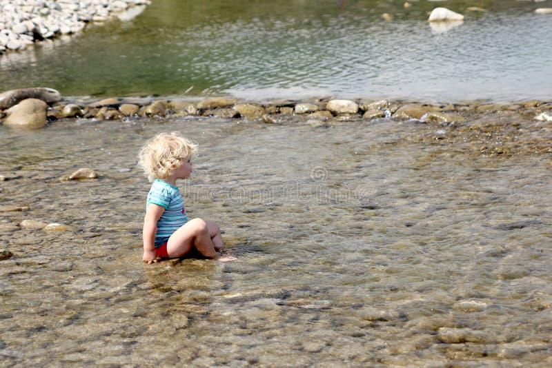 Малыш играя в реке стоковое фото rf