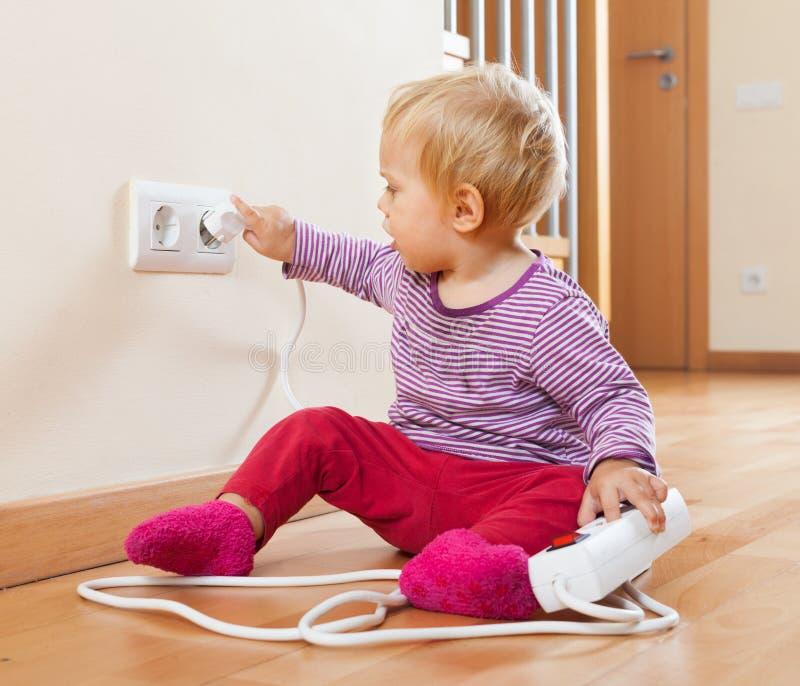 Малыш играя с удлинителем и электрическим выходом стоковая фотография