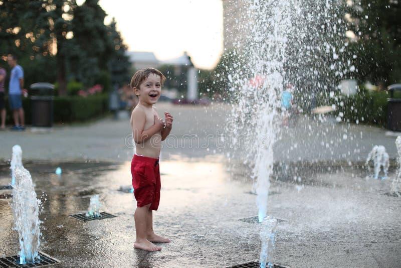 Малыш и брызгая фонтан стоковое фото rf