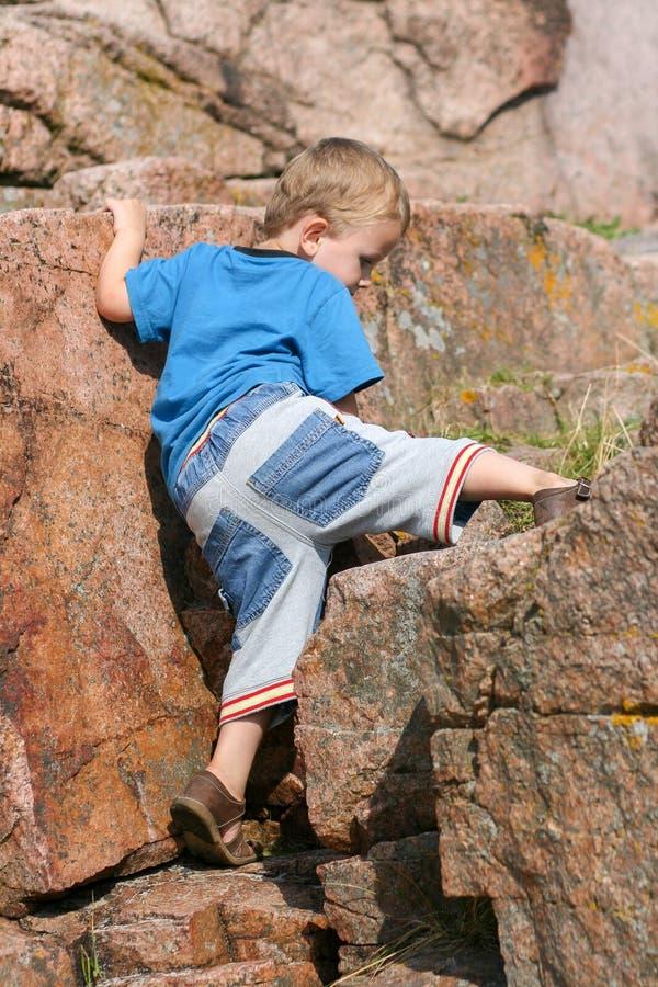 Малыш мальчика взбираясь утес стоковое изображение