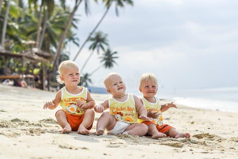 Малыш 3 младенцев сидя на тропическом пляже в Таиланде 2 мальчика и одна девушка стоковая фотография rf