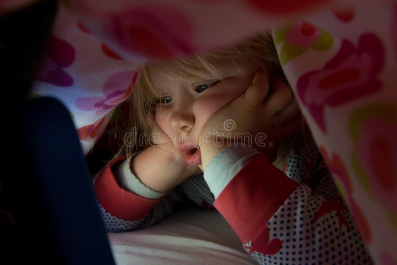Малыш под одеялом вытаращить на накаляя экране таблетки стоковые фотографии rf
