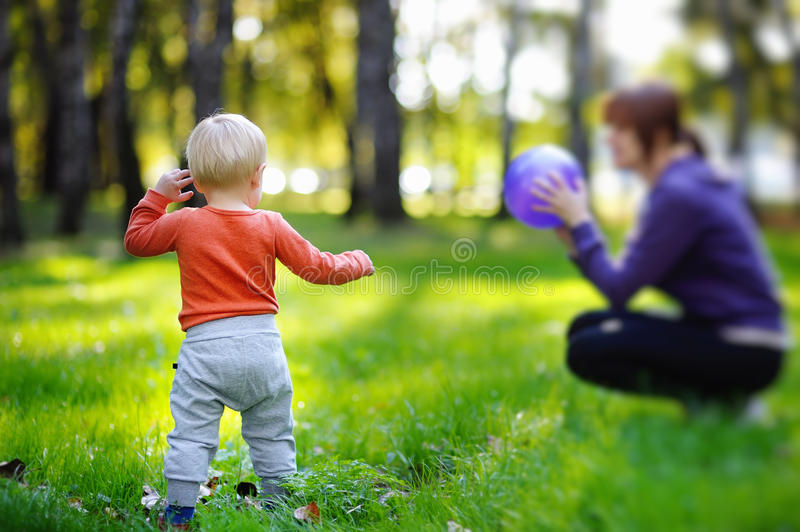 Малыш при его мать играя с шариком стоковая фотография rf