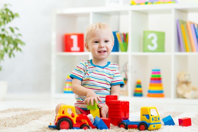 Малыш ребенк играя с автомобилем игрушки стоковая фотография