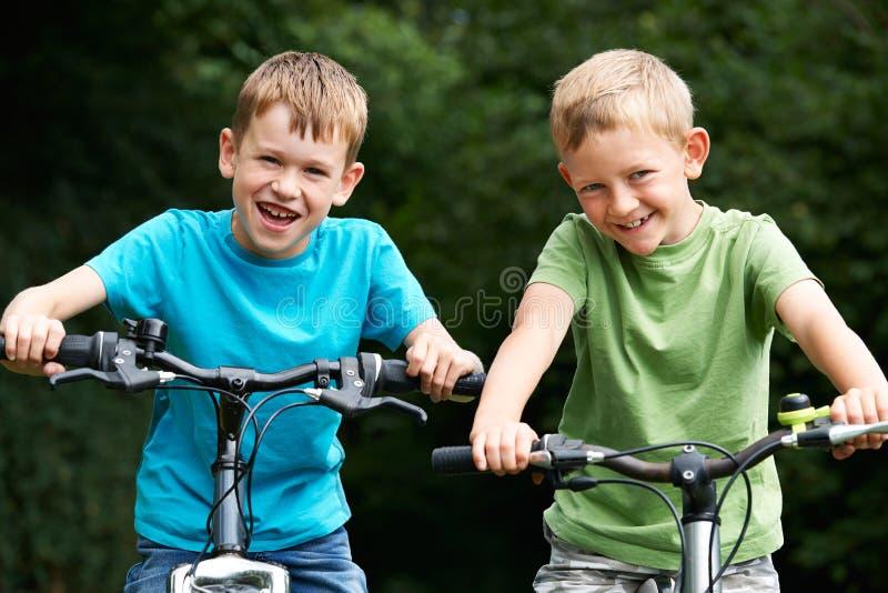 2 мальчика ехать велосипеды совместно стоковое изображение rf