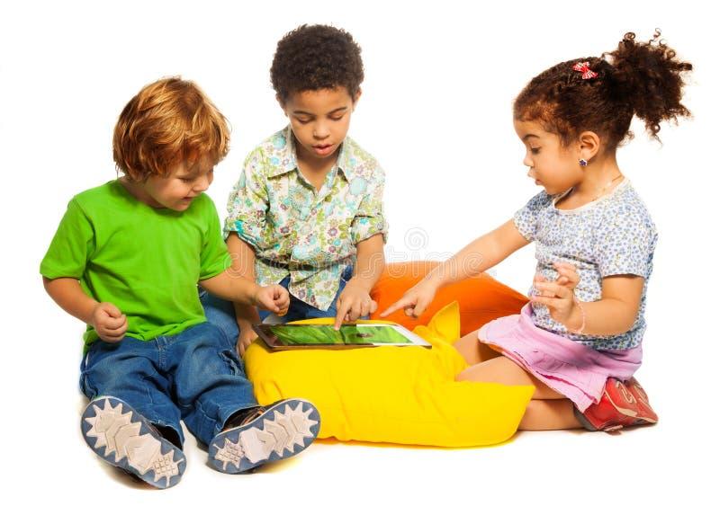 2 мальчика и девушка играя с таблеткой стоковая фотография rf