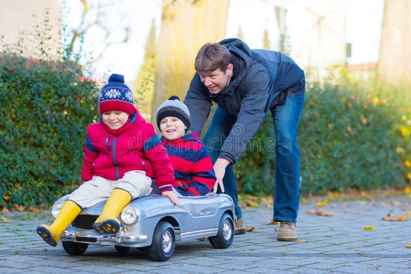 2 мальчика и отец маленьких ребеят играя с автомобилем, outdoors стоковые фотографии rf