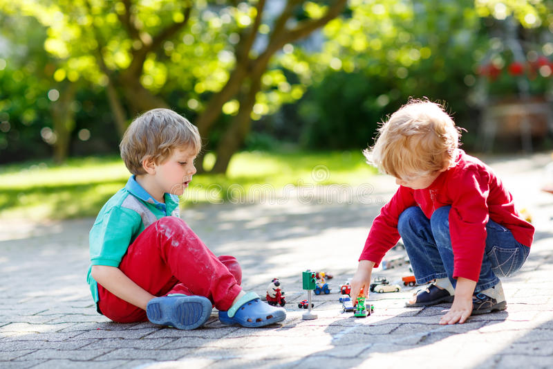 2 мальчика маленького ребенка играя с игрушками автомобиля стоковая фотография