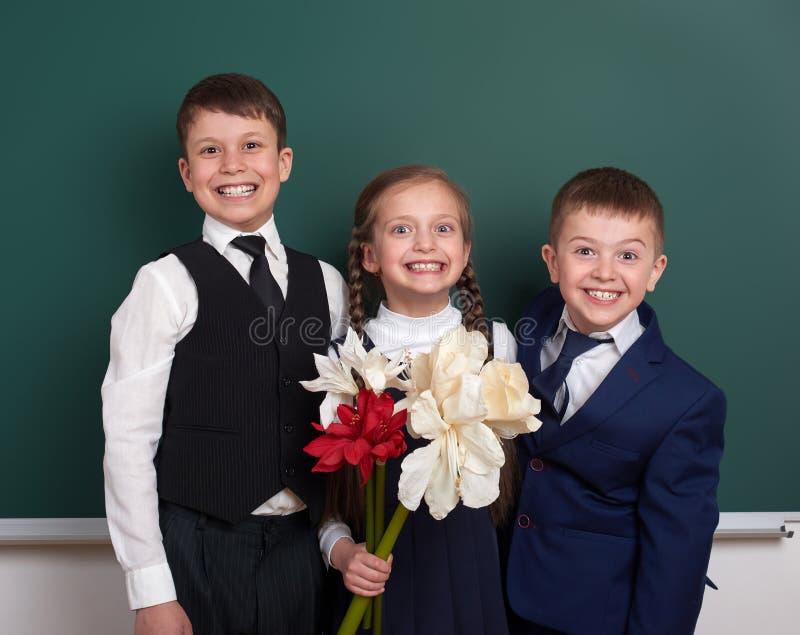 Мальчики давая девушку цветут, начальной школы около пустой предпосылки доски, одетой в классическом черном костюме, зрачок групп стоковое фото rf
