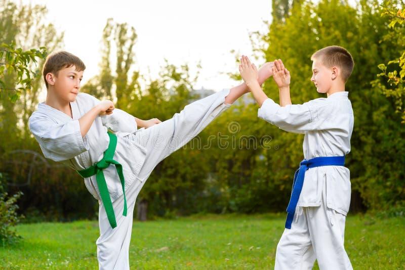 Мальчики в белом кимоно во время карате тренировки стоковая фотография
