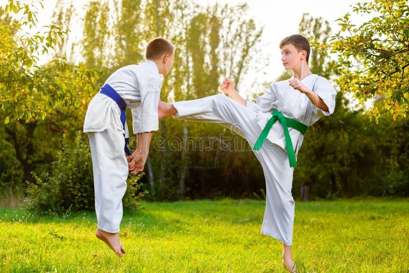 Мальчики в белом кимоно во время карате тренировки стоковое фото rf