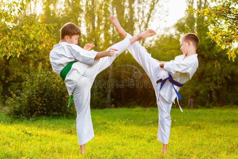 Мальчики в белом кимоно во время карате тренировки стоковая фотография rf