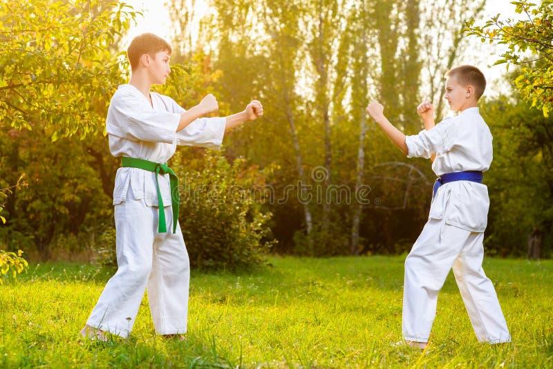 Мальчики в белом кимоно во время карате тренировки стоковое изображение rf