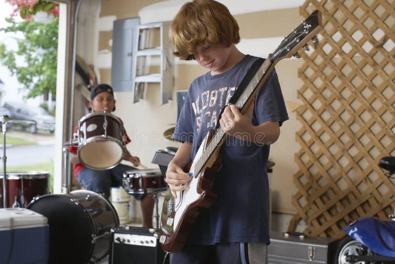 Мальчики играя барабанчик и гитару в гараже стоковое изображение rf